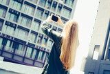 Young blond woman with smartphone in front of skyscrapers - 243944746