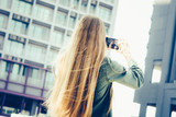 Young blond woman with smartphone in front of skyscrapers - 243944978