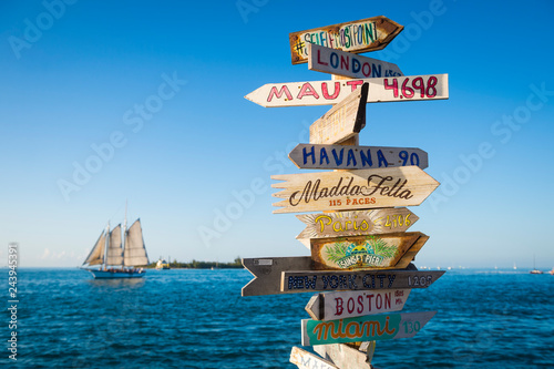 Sticker Bright scenic view of rustic wooden direction sign with sailboat in Key West, Florida, USA