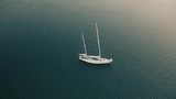 Aerial view of unknown man cruising on his sailboat with removed sails - 243955359