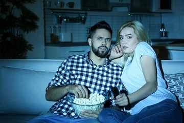 Young couple with bowl of popcorn watching TV on sofa at night