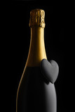 Closeup of a bottle of Champagne with a black heart against a black background - 243963732