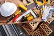 Home repairs. Construction tools, bricks and helmet top view