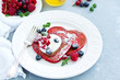 Leinwandbild Motiv Pancakes red velvet in the form of a heart with berries and cream. Valentine's Day. Selective focus.