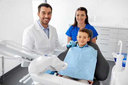 fototapeta na ścianę medicine, dentistry and healthcare concept - happy dentist, assistant and kid patient at dental clinic