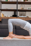 cropped view of woman practicing bridge pose at home in living room - 244041513