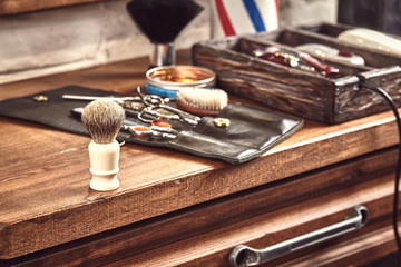 Hairdresser tools on wooden background. Top view on wooden table with scissors, comb, hairbrushes and hairclips, trimmer.