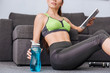 sportswoman with water bottle using digital tablet at home
