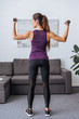 back view of sportswoman training with dumbbells at home