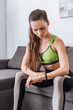 selective focus of sportswoman sitting on couch and looking at watch at home
