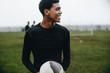 Portrait of a footballer standing on field holding a ball