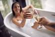 Leinwandbild Motiv drinking champagne in the bathtub- couple relaxing together in the bathtub.