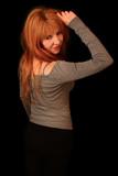 Piękna ruda dziewczyna na czarnym tle w studio - 244072986