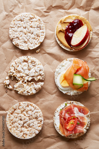 Variation of healthy gluten free rice cakes with fruit, vegetables, meat, salmon and sweets viewed from above. Top view