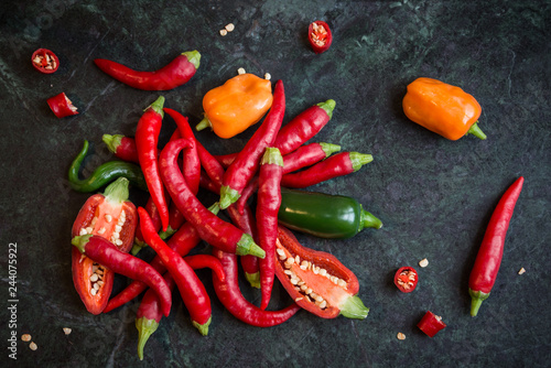 Mixed hot peppers on dark stone background - 244075922