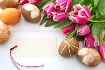 Easter card with bouquet of pink tulips and colorful eggs on white wooden . © Swetlana Wall