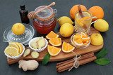 Natural flu and cold remedy with orange and lemon fruit, honey, eucalyptus oil, fresh ginger and cinnamon sticks with natural medicinal drink on bamboo background.