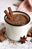 Homemade hot chocolate in a white enamel mug on a light slate, stone or concrete background.