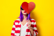 Young girl with purple hair holding heart shape on yellow background