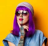Fototapeta Wieża Eiffla - Young girl with purple hair and sunglasses on yellow background © Masson