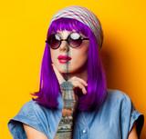 Fototapeta Fototapety z wieżą Eiffla - Young girl with purple hair and sunglasses on yellow background © Masson