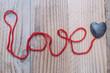 Fond love et coeur en fil rouge sur un fond bois vieilli