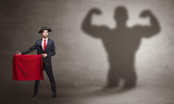 Businessman standing with red cloth on his hand and strong hero shadow on the background  - 244135574
