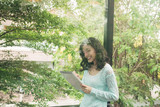 Young attractive sweet girl with notepad on a veranda. Spring mood. - 244143715