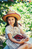 Portrait of a girl with cherries in the garden . The child holds a plate of fresh berries