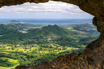 Stunning view through a rock window at the summit of famous Pali Puka hiking trail on the island of Oahu, Hawaii, USA. The dangerous hike offers breathtaking views to Kailua and Kāne'ohe in East Oahu.