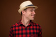 Tourist man wearing red checkered shirt and hat against brown ba