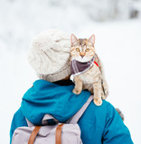 Cat sitting on shoulder of woman and staring at camera in winter.