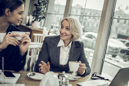 Mother and daughter feeling relieved and rested drinking coffee together