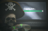 Illegal data copying concept. Cybercrime. Computer piracy background. Pirate hat, human skull, laptop and compact disc on a table. - 244165503