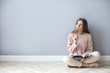 Young woman with notepad think hard sitting on a wooden floor.