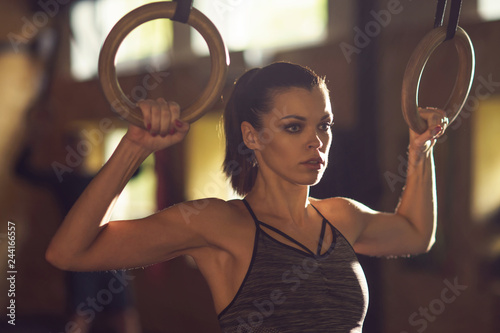 Poster Fit, sporty and athletic sportswoman working in a gym. Woman training using gymnastic rings. Sports, athletics and fitness concept.