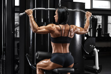 Muscular woman working out in gym doing exercise for back. Strong fitness girl, muscles back © nikolas_jkd
