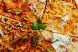 A slices on different kinds of pizza set in one rounded piece on wooden background - 244182508