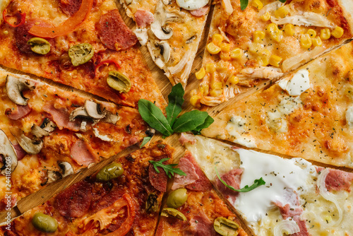 canvas print picture A slices on different kinds of pizza set in one rounded piece on wooden background