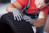 Mechanic holding a tire tire at the repair garage. replacement of winter and summer tires - 244185598