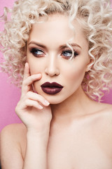 Portrait of beautiful and fashionable model girl with amazing blue eyes, with curly blonde hair and with professional bright makeup isolated at pink background at studio © innarevyako