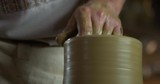 Tilting shot of potters hands rising clay jug and starting to shape it. - 244187985