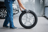 Mechanic holding a tire tire at the repair garage. replacement of winter and summer tires - 244203312