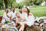 Carefree mood. Group of adult friends have a rest and conversation in the backyard of restauraunt at dinner time - 244204398