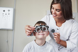 Eyes wide open. Doctor tuning the phoropter to to determine visual acuity of the little boy - 244210184