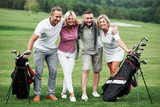 Beautiful woods at background. Photo of friends hugging and smiling with golf equipment after the game - 244218903