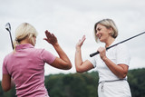 Two female golf players giving high five in the background of beautiful green woods - 244219152