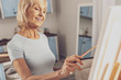 Positive delighted mature woman looking at her work