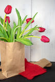 Fototapeta Tulipany - red tulips in generic paper bag on burlap fabric pieces with whitewashed wood background © 14ktgold