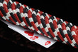 poker chips lie in a row on two playing cards, black background